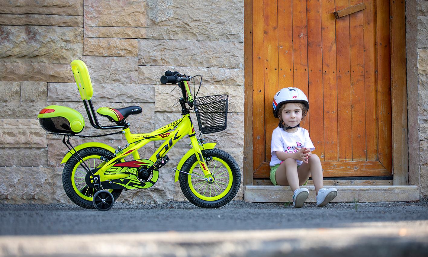 دختربچه نشسته کنار دوچرخه اوکی